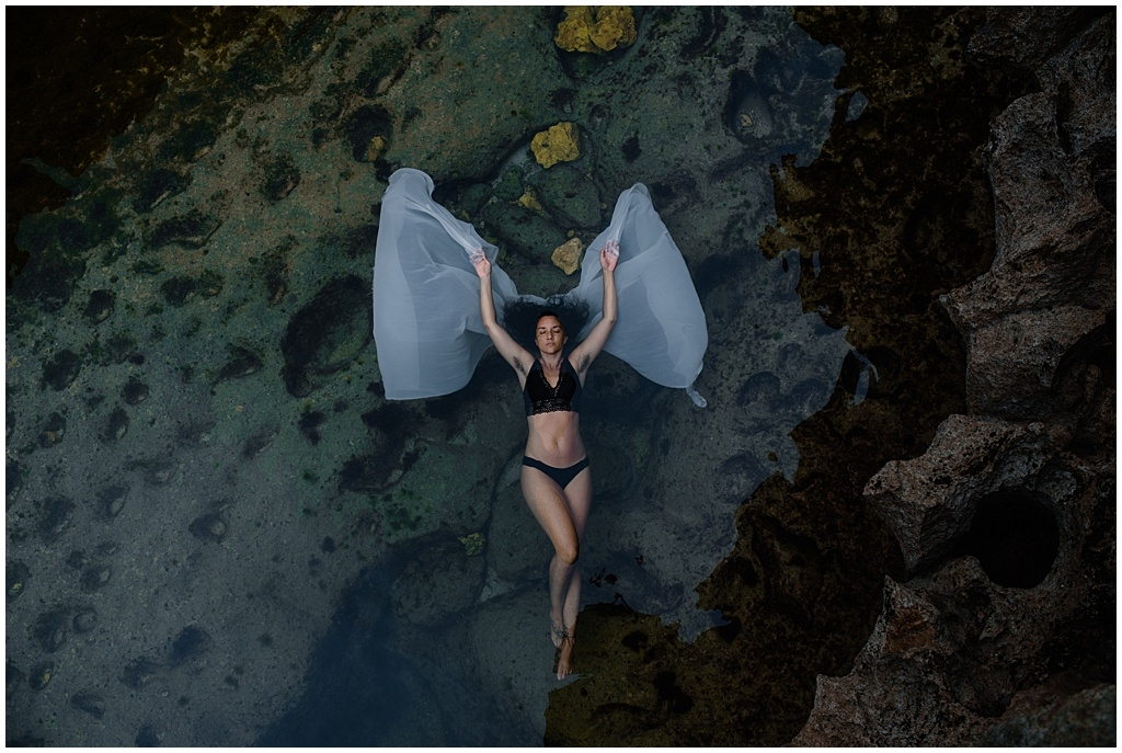 Beautiful woman floating in water with angel wings