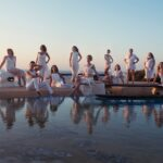 Group photo of women in white by a pool in Greece