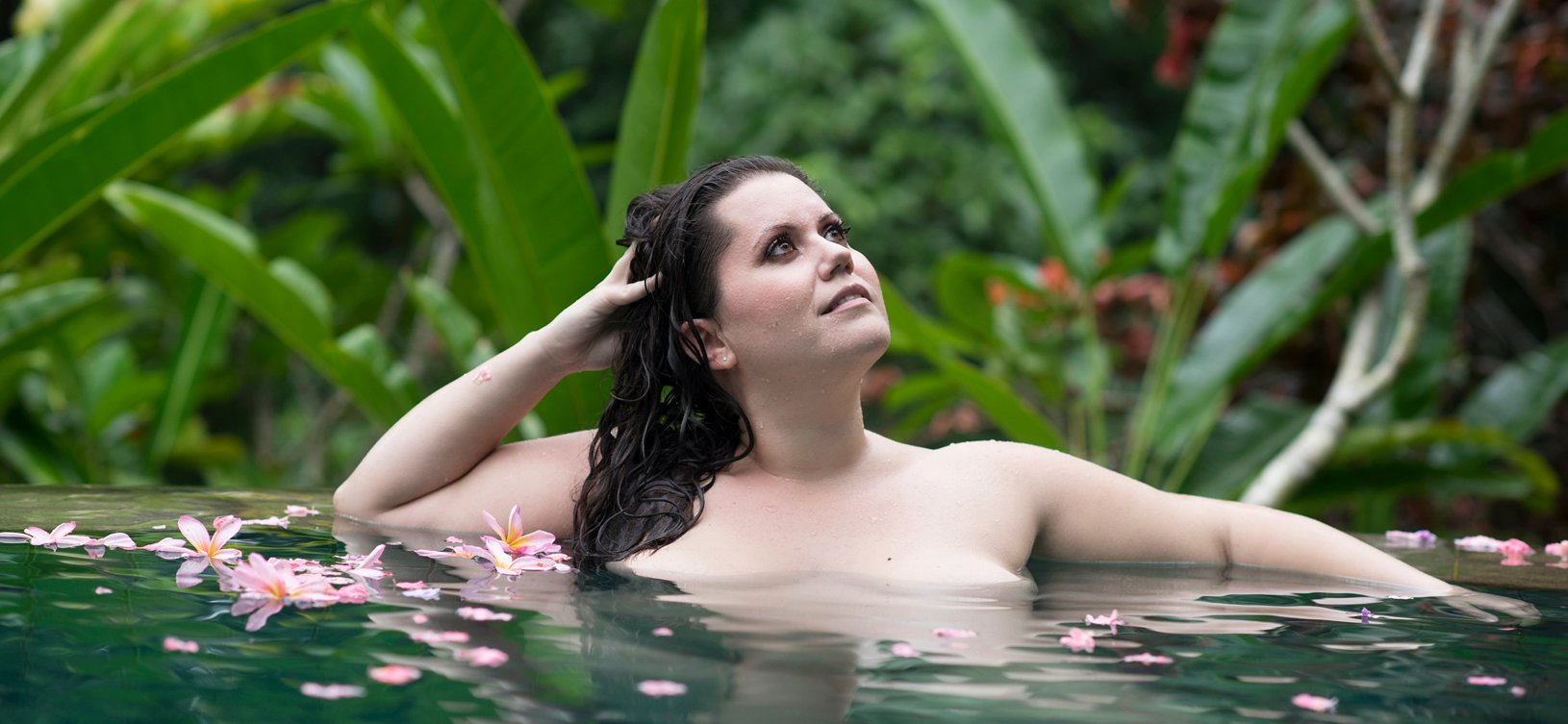 Destination boudoir photo of woman in pool with flower in her hair