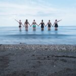 Group of women holding hands in the water
