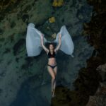 Beautiful photo of woman floating in the water at bali photo location Angel's Billabong