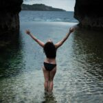 Joyful woman with her hands in the air at Angel's Billabong Nusa Penida Photo Location