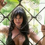 Boudoir photo of woman peeking through wrought iron door