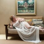 Plus size boudoir photo of woman laughing in a white sheet